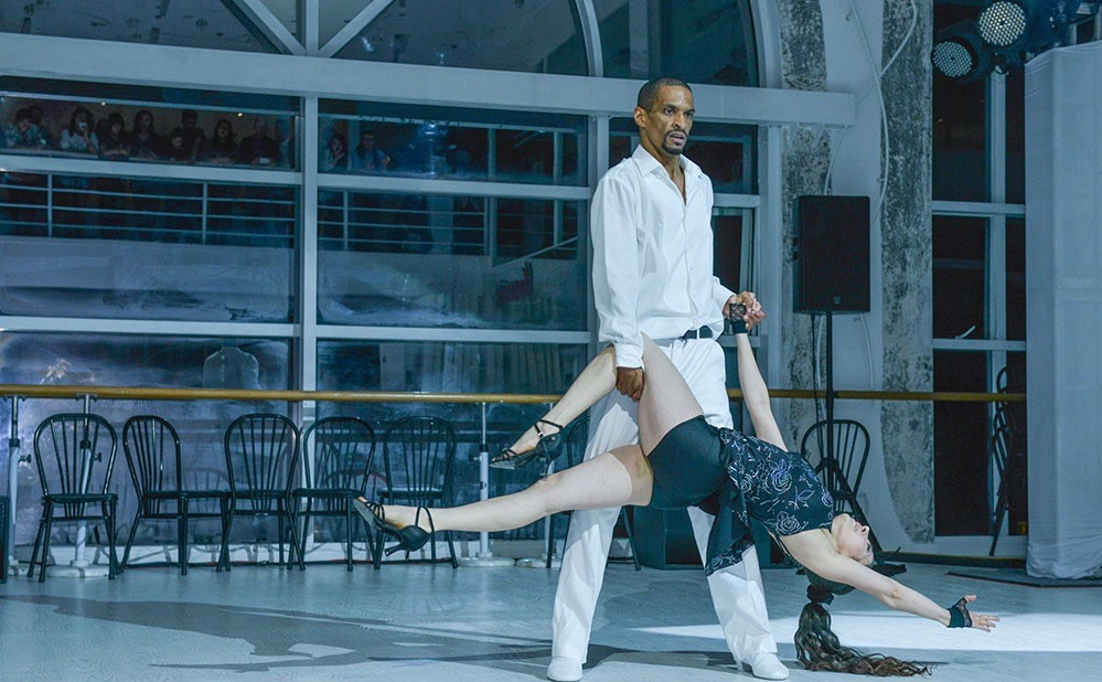 Man with white salsa dance shoes hold a lady with black salsa dance shoes