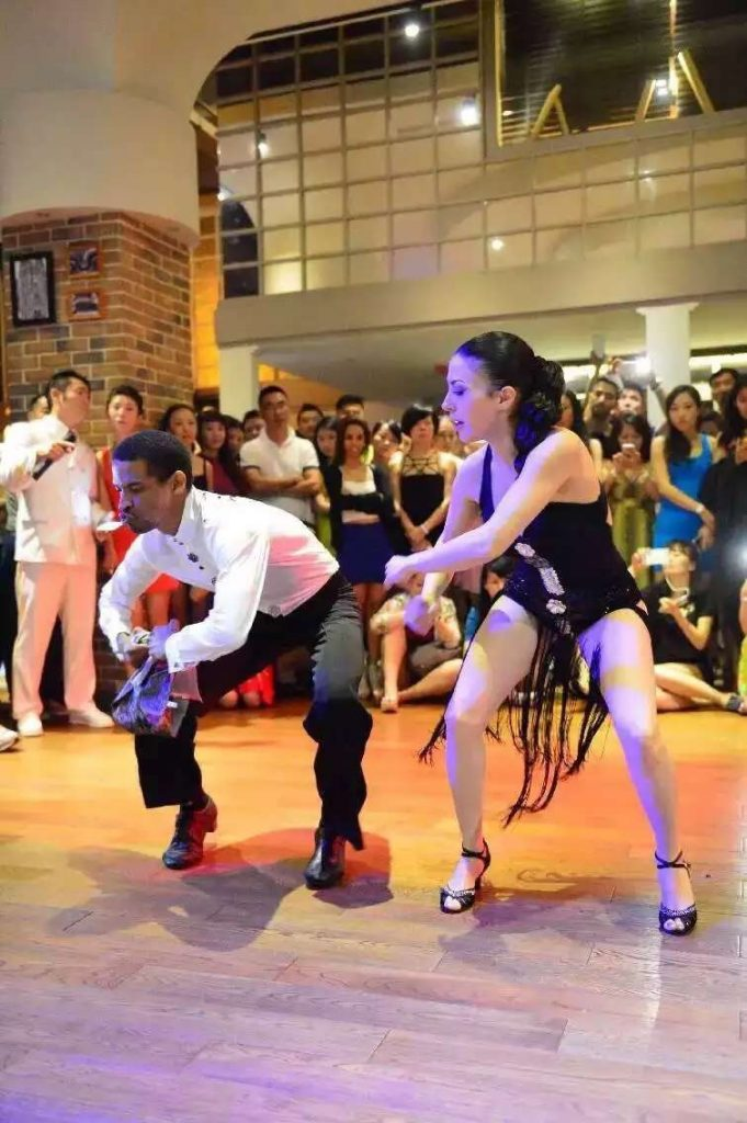 A man and lady execute a rumba move in salsa rueda
